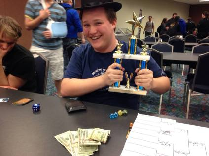 Collin Rountree holding trophy wearing hat showing cash